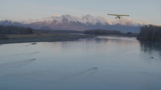AK0001_0311 - 4K stock footage aerial video orbiting a small plane readying for takeoff on the shore, Knik River, Alaska, sunset