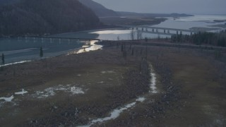 AK0001_0313 - 4K stock footage aerial video flying over the forest, revealing two bridges spanning the Knik River, Alaska, twilight