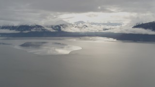 AK0001_0351 - 4K stock footage aerial video snowy Kenai Mountains, sunlit clouds, the Turnagain Arm of the Cook Inlet, Alaska