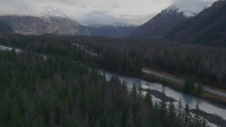 AK0001_0388 - 4K stock footage aerial video flying low over forest, revealing river, Portage Glacier Road, Portage Lake, Alaska