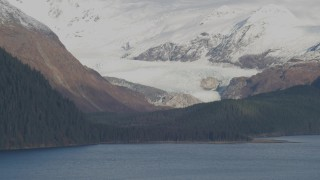 AK0001_0398 - 4K stock footage aerial video fly by glacier near shore, snowy Chugach Mountain peaks, Passage Canal, Alaska