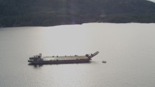 AK0001_0404 - 4K stock footage aerial video approaching an anchored barge, reveal surrounding foothills, Shotgun Cove, Alaska