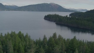 AK0001_0406 - 4K stock footage aerial video forested shoreline of Prince William Sound, to open water, Passage Canal, Alaska