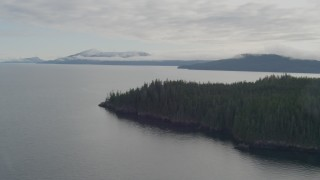AK0001_0407 - 4K stock footage aerial video flying out to open water, pan right to shoreline, Passage Canal, Alaska