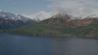 AK0001_0408 - 4K stock footage aerial video forested shoreline, snow capped Chugach Mountains, Prince William Sound, Alaska