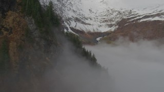 AK0001_0416 - 4K stock footage aerial video fly above fog, approach Chugach Mountain peak, Prince William Sound, Alaska