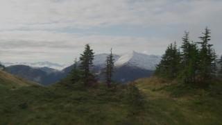 AK0001_0423 - 4K stock footage aerial video over tree lined ridge, river valley, snowy peaks, Prince William Sound, Alaska