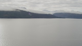 AK0001_0429 - 4K stock footage aerial video crossing a bay, approach forested peaks, clouds, Prince William Sound, Alaska