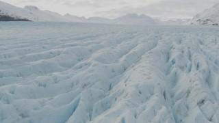 AK0001_0437 - 4K stock footage aerial video tilt up from surface of glacier, reveal snowy peaks, Prince William Sound, Alaska