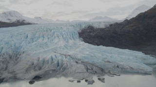 AK0001_0448 - 4K stock footage aerial video fly by a glacier spilling over ridge into lake, Prince William Sound, Alaska