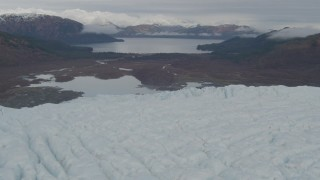 AK0001_0451 - 4K stock footage aerial video flying over glacier with a view of the tree lined show, Prince William Sound, Alaska