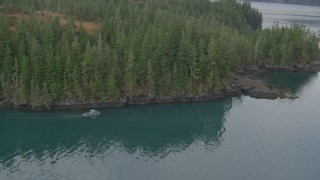 AK0001_0458 - 4K stock footage aerial video fly by boat cruising the shoreline, out over the bay, Prince William Sound, Alaska