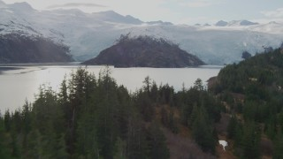 AK0001_0470 - 4K stock footage aerial video approaching island, reveal glaciers spilling over shore, Blackstone Bay, Alaska