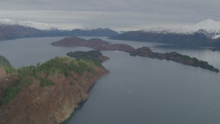 AK0001_0480 - 4K stock footage aerial video flying by island, surrounded by snow capped mountains, Blackstone Bay, Alaska