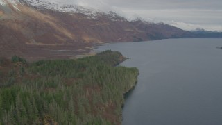 AK0001_0482 - 4K stock footage aerial video fly over forested shoreline, approach snow capped peaks, Blackstone Bay, Alaska