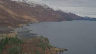 AK0001_0484 - 4K stock footage aerial video follow shoreline, approaching snow capped peaks, Blackstone Bay, Alaska