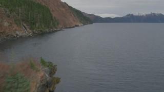 AK0001_0487 - 4K stock footage aerial video flying by steep slope of mountain peak on shore, Blackstone Bay, Alaska
