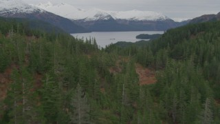 AK0001_0493 - 4K stock footage aerial video flying over wooded hills, revealing Shotgun Cove, barge, Blackstone Bay, Alaska