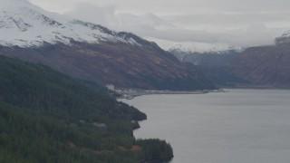 AK0001_0496 - 4K stock footage aerial video flying along wooded shoreline, approaching Whittier, Alaska