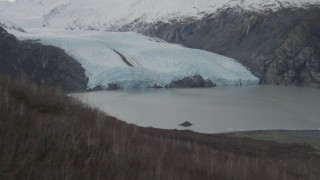 AK0001_0504 - 4K stock footage aerial video ascending grassy ridge, approach Portage Lake, base of Portage Glacier, Alaska