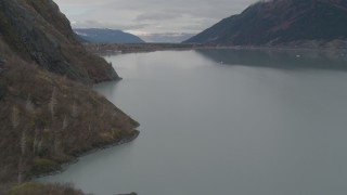 AK0001_0506 - 4K stock footage aerial video flying along rocky slope, approach building, Portage Lake, Alaska