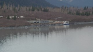 AK0001_0507 - 4K stock footage aerial video flying low over water, by a docked boat, Portage Lake, Alaska