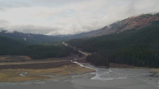 AK0001_0523 - 4K stock footage aerial video flying by Seward Highway cutting through forest in the valley, Portage, Alaska
