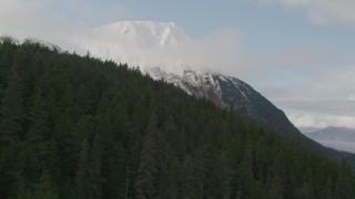 AK0001_0524 - 4K stock footage aerial video ascending a wooded slope, revealing snow capped peak, Kenai Mountains, Alaska