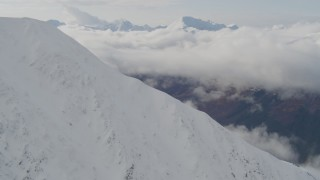 AK0001_0528 - 4K stock footage aerial video rounding snowy summit, reveal cloud covered Kenai Mountains, Alaska