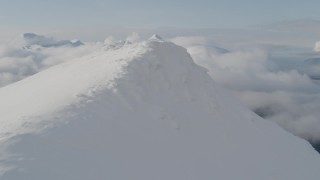 AK0001_0530 - 4K stock footage aerial video flying over snowy summit, revealing thick clouds, Kenai Mountains, Alaska