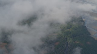 AK0001_0531 - 4K stock footage aerial video bird's eye view over clouds, river valley, wooded foothills, Kenai Mountains, Alaska
