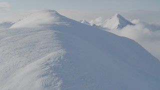 AK0001_0534 - 4K stock footage aerial video flying through low clouds up the summit of a peak, Kenai Mountains, Alaska