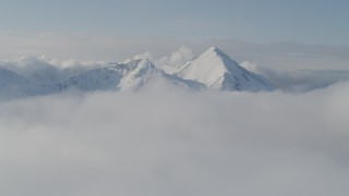 AK0001_0535 - 4K stock footage aerial video flying by snow covered Kenai Mountains, low clouds, Kenai Mountains, Alaska