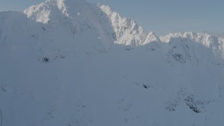 AK0001_0538 - 4K stock footage aerial video flying over snowy ridge, revealing mountain peaks, Kenai Mountains, Alaska