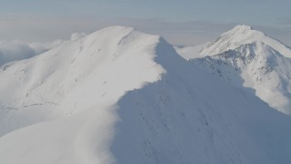 AK0001_0539 - 4K stock footage aerial video approaching snowy mountains, flying up a snowy slope, Kenai Mountains, Alaska