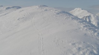 AK0001_0540 - 4K stock footage aerial video flying up snowy slope, reveal mountain range below, Kenai Mountains, Alaska