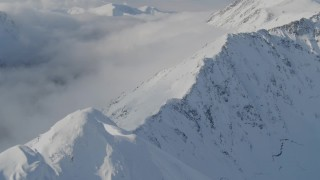 AK0001_0541 - 4K stock footage aerial video descending a snowy ridge, approaching low clouds, Kenai Mountains, Alaska
