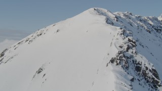 AK0001_0542 - 4K stock footage aerial video ascending a snowy ridge, flying along the slopes, Kenai Mountains, Alaska