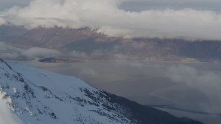 AK0001_0543 - 4K stock footage aerial video snowy summit, reveal Turnagain Arm of the Cook Inlet, Kenai Mountains, Alaska
