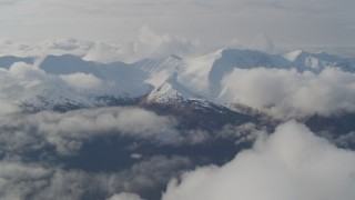 AK0001_0547 - 4K stock footage aerial video flying by low clouds over valley bordered by the Kenai Mountains, Alaska