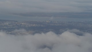 AK0001_0566 - 4K stock footage aerial video flying over snowy ridge, low clouds, reveal Anchorage, Chugach Mountains, Alaska