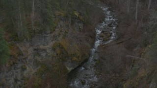 AK0001_0632 - 4K stock footage aerial video following river at bottom of gorge, reveal wooded hills, Birchwood, Alaska