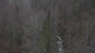 AK0001_0637 - 4K stock footage aerial video flying over forested hills, tilt down on river, Birchwood, Alaska