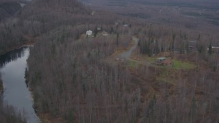 AK0001_0650 - 4K stock footage aerial video approaching homes atop wooded hills, near river, distant valley, Birchwood, Alaska