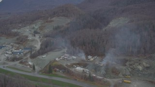AK0001_0652 - 4K stock footage aerial video flying away from a quarry, wooded hills, Chugiak, Alaska