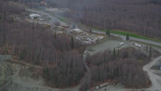 AK0001_0655 - 4K stock footage aerial video fly away from rock quarry, hillside with excavator, Chugiak, Alaska