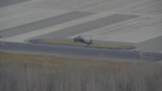 AK0001_0668 - 4K stock footage aerial video military helicopter landing, 6 parked, Bryant Army Heliport, Anchorage, Alaska