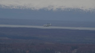 AK0001_0671 - 4K stock footage aerial video tracking E-3 Sentry  landing, snowy mountains, Fort Richardson, Alaska