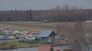 AK0001_0686 - 4K stock footage aerial video tracking small plane taking off, Lake Hood Seaplane Base, Anchorage, Alaska