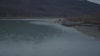 AK0001_0704 - 4K stock footage aerial video flying low over river, approaching tree-lined shore, winter, Knik River, Alaska